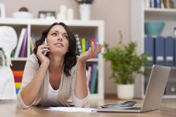 Verzweifelte Frau mit Handy, Laptop und Unterlagen